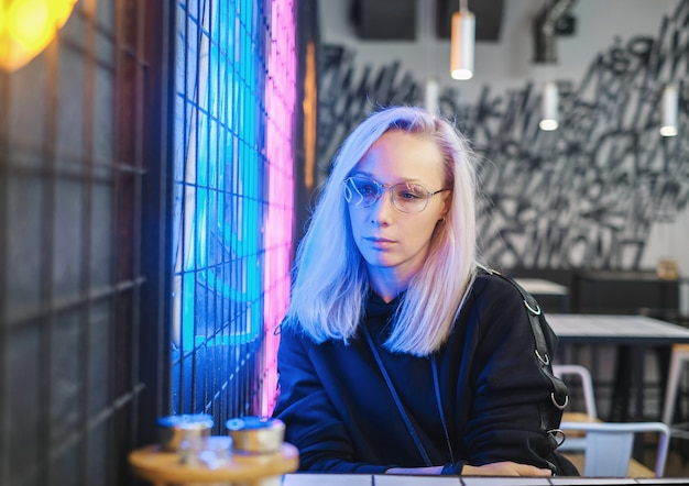 Sad hipster blonde girl in glasses sitting in bar near the neon