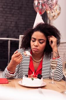 Печальный праздник. несчастная мрачная женщина смотрит на кусок торта во время грустной вечеринки по случаю дня рождения