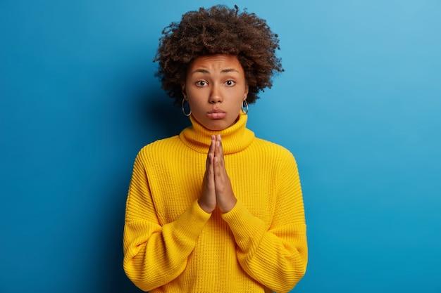 Triste donna speranzosa con la pettinatura riccia tiene le mani unite in segno di speranza, fa un gesto di preghiera, ha bisogno di sostegno e aiuto