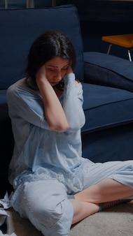 Грустная безнадежная молодая женщина, сидящая одна дома в отчаянии, подавленная, расстроенная, подчеркнула су ...