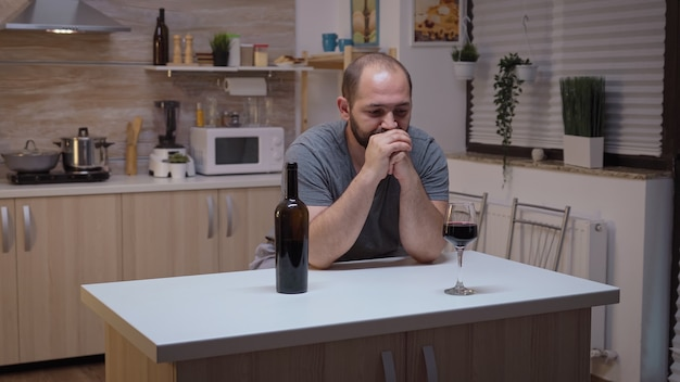 Sad husband drinking red wine sitting in the kitchen. unhappy person suffering of migraine, depression, disease and anxiety feeling exhausted with dizziness symptoms having alcoholism problems.