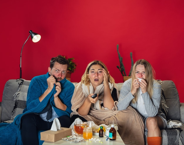 슬퍼. 열이 나고 감기에 걸린 아픈 젊은이들이 괴로워합니다. 아프고, 파랗고, 코를 킁킁거립니다. 감기, 바이러스, 계절 그립. 남자와 여자는 집에서 꿀, 차, 약을 함께 소파에 앉아 있습니다.