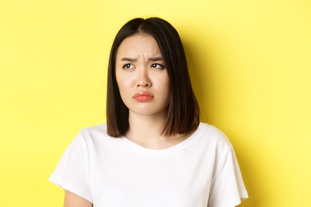 Sad and jealous asian girl sulking, frowning and looking left with upset face, standing over yellow.