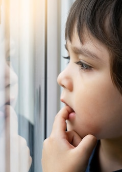 Sad kid boy putting finger in his mouth and looking out of the window