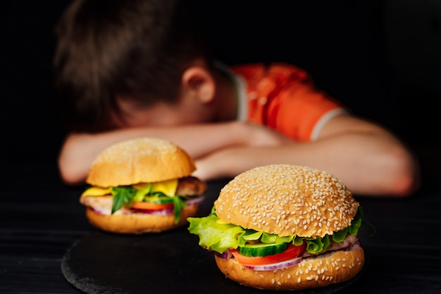 Sad kid sitting at the table and puts his head on arms in front of tasty burgers.