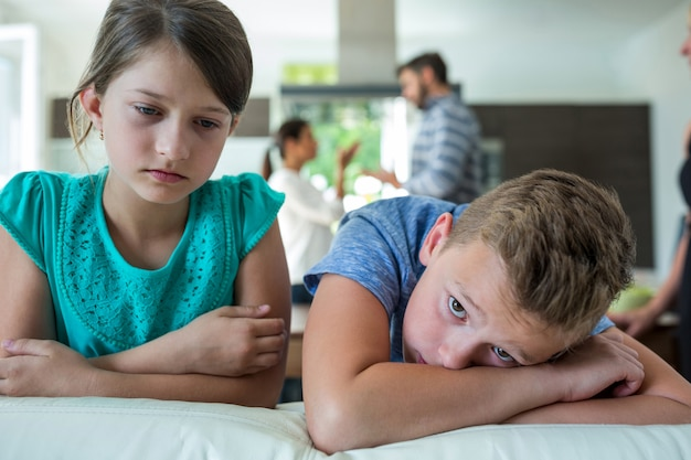Sad kids leaning on sofa while parents arguing