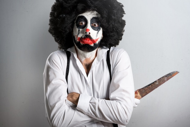 Sad killer clown with knife on textured background