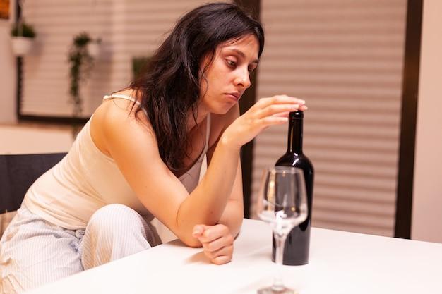 台所で一人で飲んでいる悲しい女性。片頭痛、うつ病、病気、不安感に苦しんでいる不幸な人は、アルコール依存症の問題を抱えているめまいの症状で疲れ果てています。