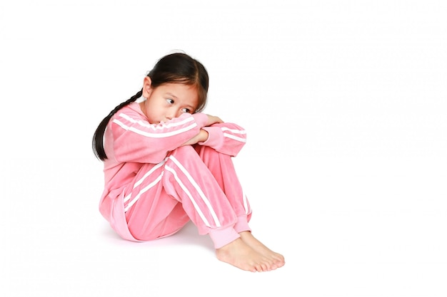 Sad little asian child girl in pink tracksuit or sport cloth sitting and hugging knees
