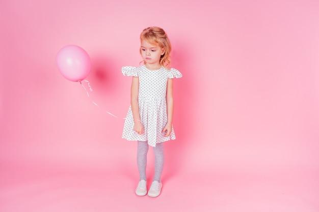 ピンクの背景、誕生日のお祝い、悲しみと失望の悲しみのスタジオでバルーンを保持しているエンドウ豆の白いドレスを着た悲しい小さなブロンドの女の子4-5歳。