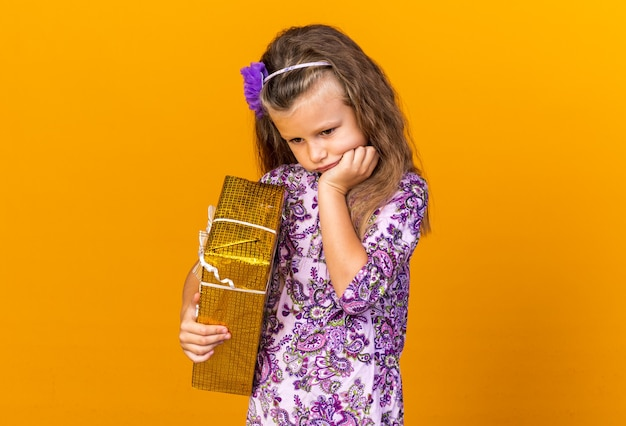 Sad little blonde girl putting hand on chin and holding gift box isolated on orange wall with copy space