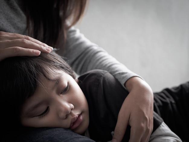 집에서 그의 어머니에 의해 안고있는 슬픈 작은 소년. 사랑, 가족 개념.