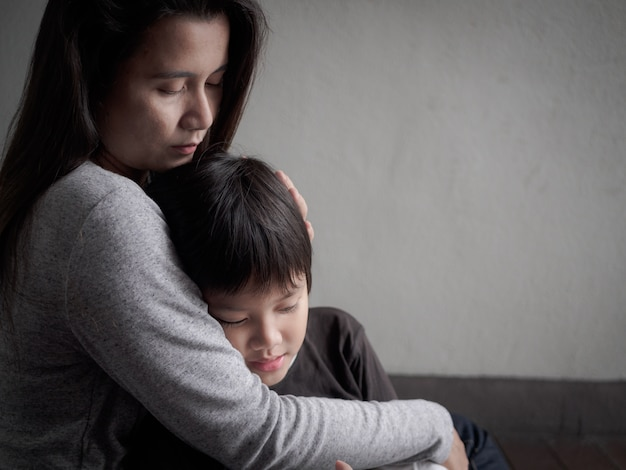 Sad little boy being hugged by his mother at home. parenthood, love concept.