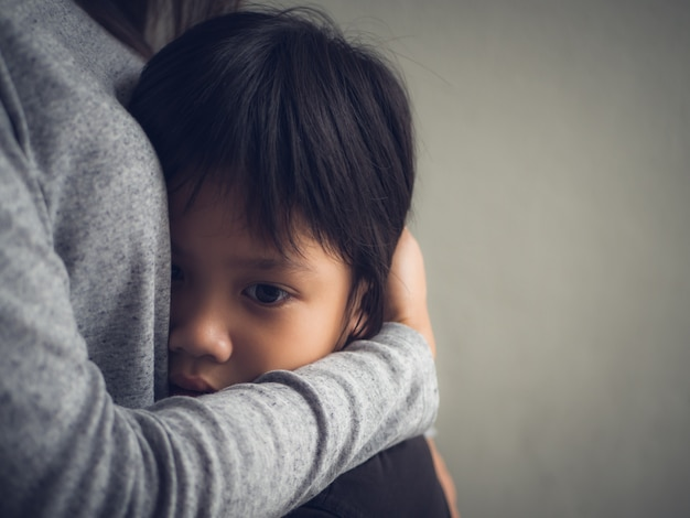 Sad little boy being hugged by his mother at home.