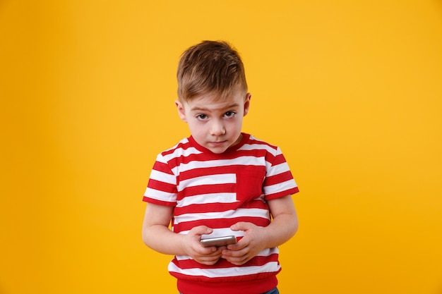 Telefono cellulare triste della tenuta del ragazzino