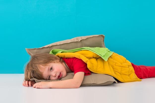 家でハンバーガーのように横たわっている悲しい少年