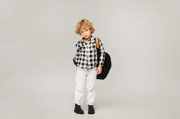 Sad little boy in shirt and jeans with backpack isolated.
