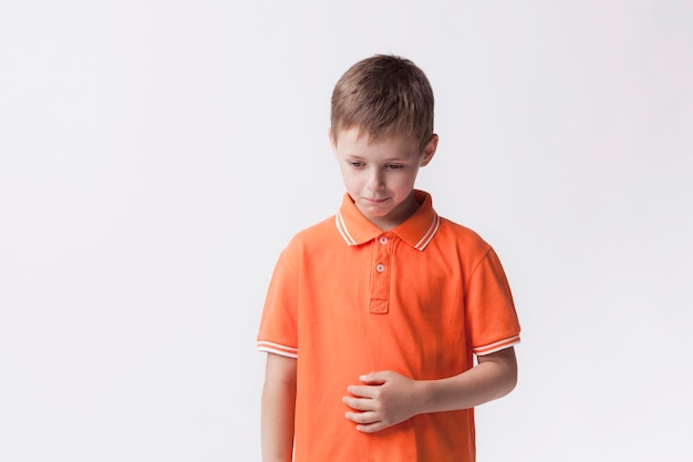 Sad little boy standing near white wall having stomach pain