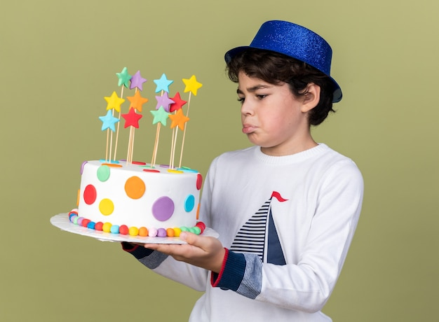 Sad little boy wearing blue party hat holding and looking at cake
