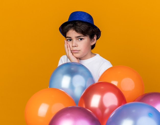 Sad little boy wearing blue party hat standing behind balloons putting hand on cheek isolated on orange wall
