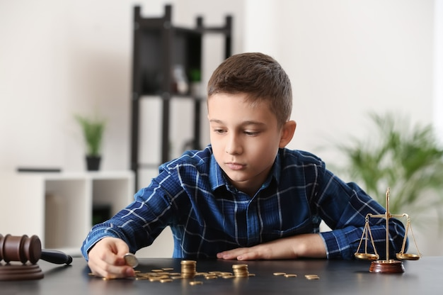 Sad little boy with coins sitting at table in lawyer's office.
