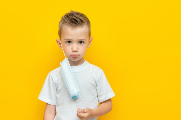 Грустный маленький мальчик с не полностью одетой медицинской маской