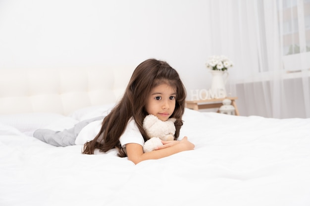 Sad little brunette girl lying with teddy bear on bed at home.