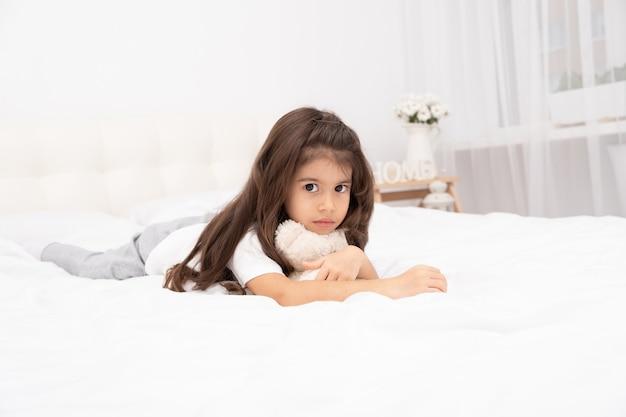 自宅のベッドでテディベアと横になっている悲しい小さなブルネットの少女。