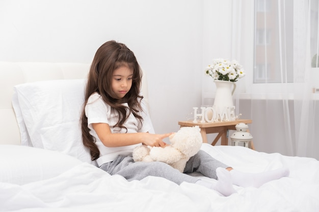 Sad little brunette girl sitting with teddy bear on bed at home.