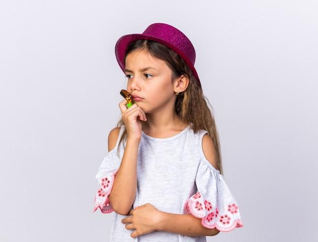 Triste piccola ragazza caucasica con cappello viola partito che tiene il fischio del partito e guardando il lato isolato sulla parete bianca con lo spazio della copia