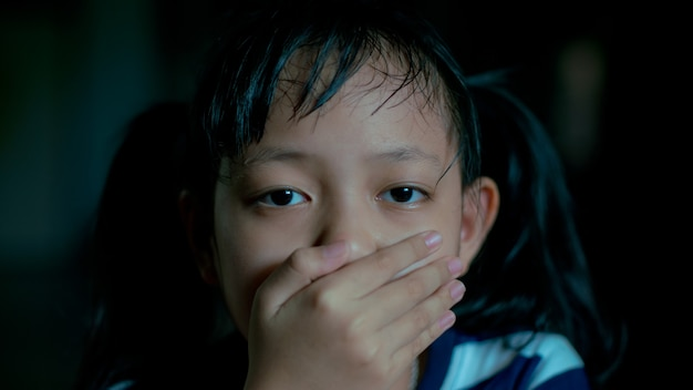 Sad little child girl covering her mouth with hands in dark room.