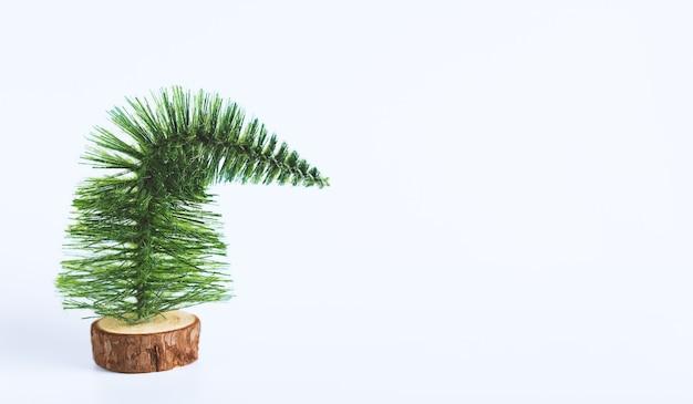 白いスペースに悲しい小さなクリスマスツリー。気分の悪いコンセプト