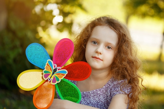 Sad little curly girl holding a rainbow pinwheel toys in spring park.