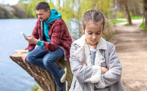 Грустная маленькая девочка, потому что папа проверяет свой телефон, гуляя по лесу, и не обращает на нее внимания.