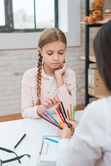 Sad little girl choosing the colored pencils hold by female psychologist