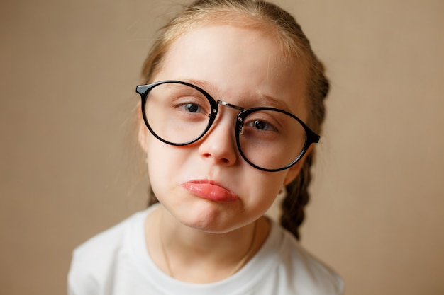 Sad little girl in glasses is looking with serious face at camer