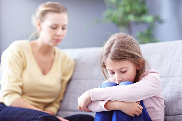 Sad little girl and her mom at home