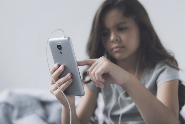Sad little girl is looking at the phone.