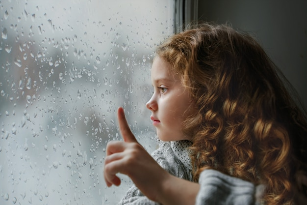 Sad little girl looking out the window on rain drops near wet glass autumn bad weather.