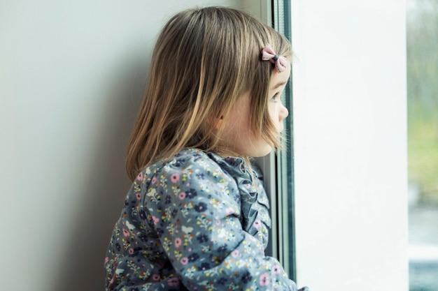 Грустная маленькая девочка смотрит в окно. ребенок 3 лет в платье. крупный план. одиночество и грусть.