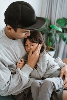 Sad little girl resting on her father's chest