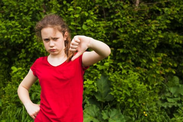 Грустная маленькая девочка показывает жест неприязни в парке