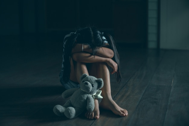 Sad little girl sitting alone with teddy bear on floor