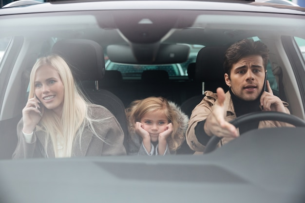 Грустная маленькая девочка сидит в машине, пока ее родители разговаривают