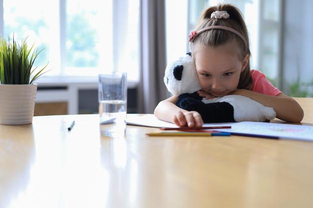 Грустная маленькая девочка, сидящая за столом с игрушечным медведем пандой, сидя в гостиной дома.
