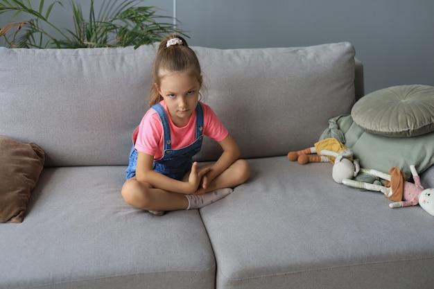 Грустная маленькая девочка сидит на диване в одиночестве дома.