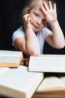 Грустная маленькая девочка сидит с кучей книг. знания и образование.