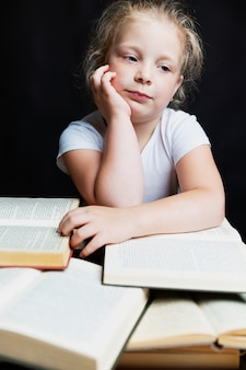 Sad little girl sitting with a pile of books. knowledge and education. black background. vertical.