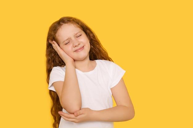 노란색 배경에 귀가 아픈 슬픈 어린 소녀. 귀 통증 개념입니다.