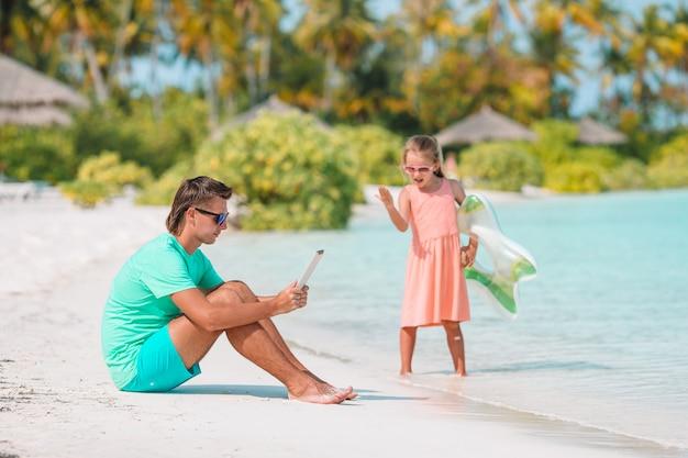 ラップトップで働いているお父さんが泳いだり、ビーチで楽しんだりするのを待っている悲しい小さな子供たち